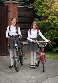 Słodkie uśmiechnięte dziewczyny chodzą do szkoły z rowerami
