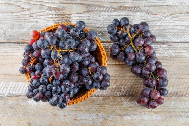 Słodkie winogrona w wiklinowym koszu na drewnianym tle. leżał płasko.