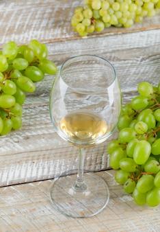 Słodkie winogrona z napojem z bliska na drewnianym tle