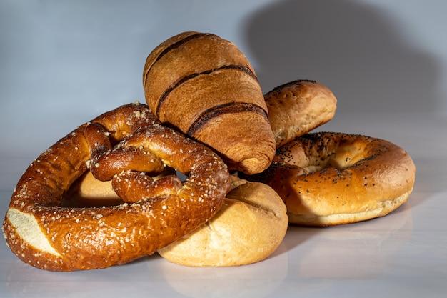 Słodkie wypieki drożdżowe. bajgle, pączki croissanty precle. na jasnym tle. skopiuj miejsce.