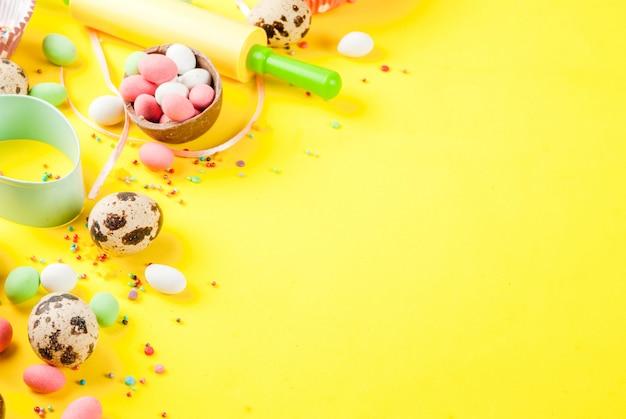 Słodkie wypieki na wielkanoc, gotowanie z pieczeniem z wałkiem do ciasta, trzepaczka do ubijania, foremki do ciastek, jajka przepiórcze, posypanie cukrem. jasny żółty, lato
