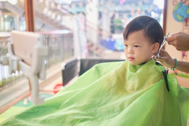 Słodkie zmartwione małe azjatyckie dziecko w wieku 3–4 lat, maluch dostaje fryzurę