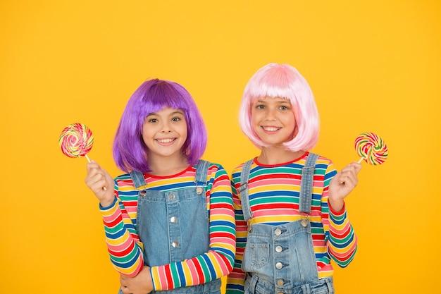 Słodkie życie. koncepcja anime cosplay party. szczęśliwe dziewczynki. fan anime. dzieciaki ze sztucznymi fryzurami jedzące lizaki. konwencja anime. żywe postacie fantastyczne motywy. współczesne dzieciństwo.