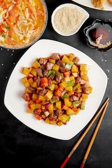 Słodko-kwaśna kaczka z warzywami i pieprzem na talerzu