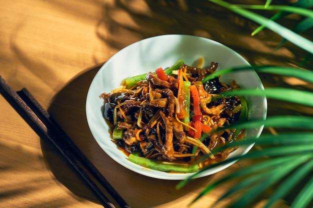 Słodko-kwaśna wieprzowina z warzywami z woka w białej misce. chiński kuzyn.