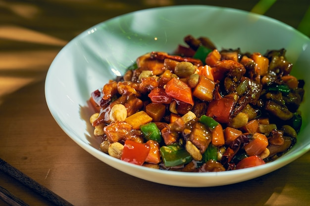 Słodko-kwaśny kurczak z warzywami z woka, sezamem i pieprzem syczuańskim w białej misce. chiński kuzyn