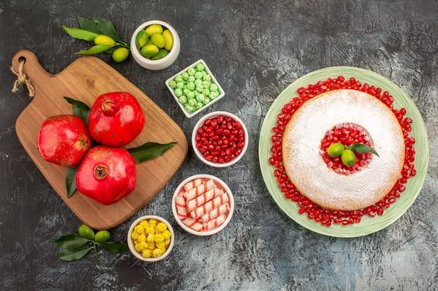 Słodycze apetyczne ciasto słodycze granaty na desce do krojenia owoce cytrusowe