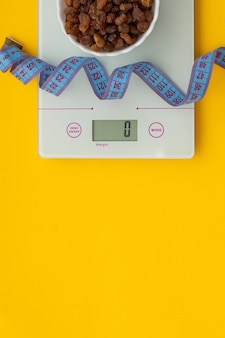Słodycze dietetyczne bez cukru, centymetrowa taśma, łuski na żółtym tle. pojęcie zdrowej diety, kontrola wagi. tracić na wadze. widok z góry
