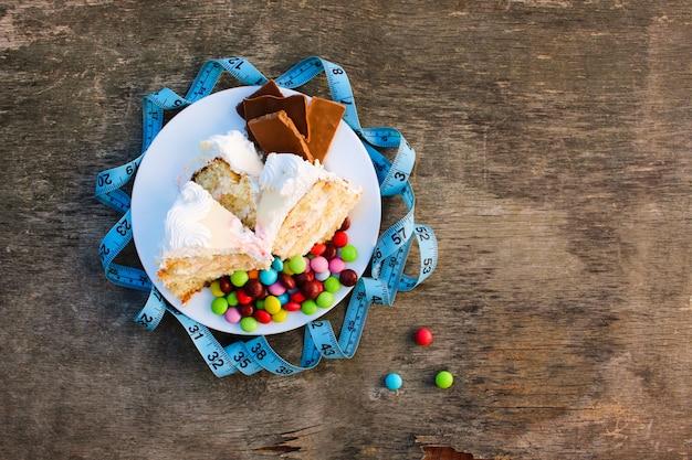 Słodycze i taśma pomiarowa na stole.