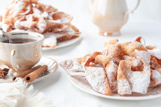 Słodycze karnawałowe chenchi na białym talerzu. posypane cukrem pudrem. w pobliżu znajduje się filiżanka herbaty ozdobiona cynamonem. białe tło.