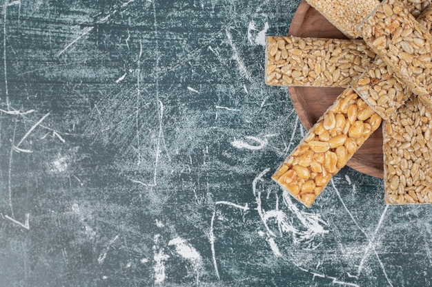 Słodycze kozinaki z nasionami i orzechami na drewnianym talerzu. wysokiej jakości zdjęcie