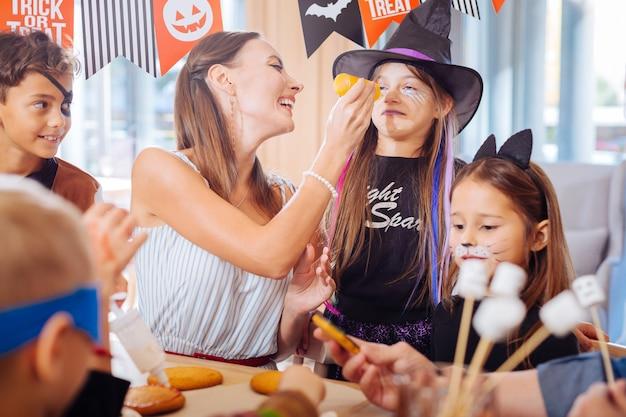 Słodycze na halloween. ciemnowłosa mama bawi się z dziećmi przy robieniu halloweenowych cukierków na rodzinne przyjęcie