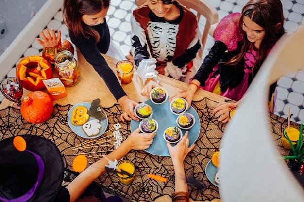 Słodycze na halloween. widok z góry dzieci w kostiumach siedzących przy stole i jedzących słodycze na halloween