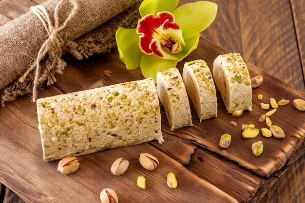 Słodycze orientalne - chałwa z pistacjami podawana z kwiatami orchidei.