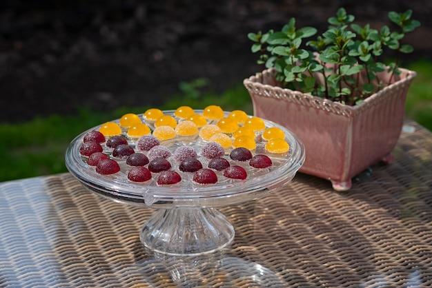 Słodycze owocowe i jagodowe, słodycze galaretowe na przezroczystym szklanym stojaku do ciasta z miętą w doniczce.