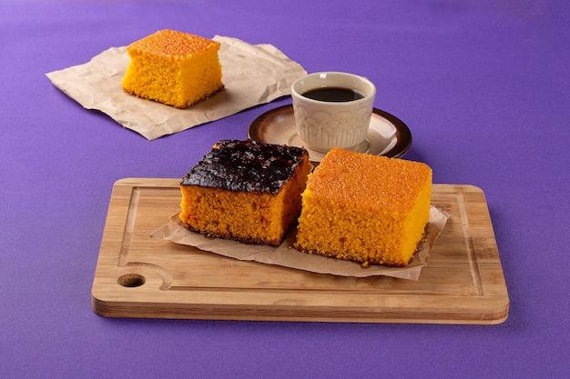 Słodycze piekarnicze na drewnianej desce z ciastem marchewkowym i francuskim chlebem w tle obok filiżanki o