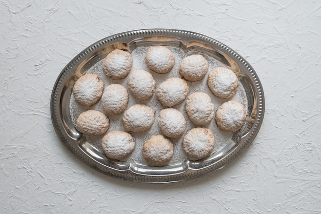 """Słodycze ramadan podawane są z herbatą na białym stole. egipskie ciasteczka """"kahk el eid"""" - ciasteczka z islamskiej uczty el fitr. widok z góry."""