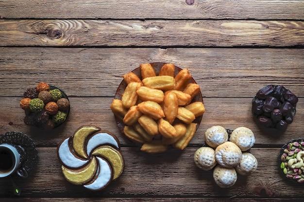 Słodycze ramadan układane są na drewnianym stole. widok z góry.