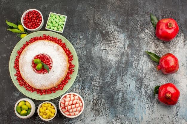 Słodycze talerz ciastek miski cukierków i limonek obok czerwonych granatów