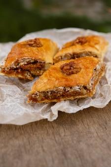 Słodycze wschodnie. deser baklawa, udekorowany orzechami na wierzchu, na papierze do pieczenia i drewnianym stole