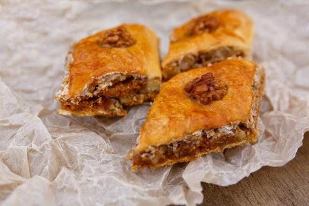 Słodycze wschodnie - deser z baklawy, na wierzchu ozdobiony orzechami, na papierze do pieczenia