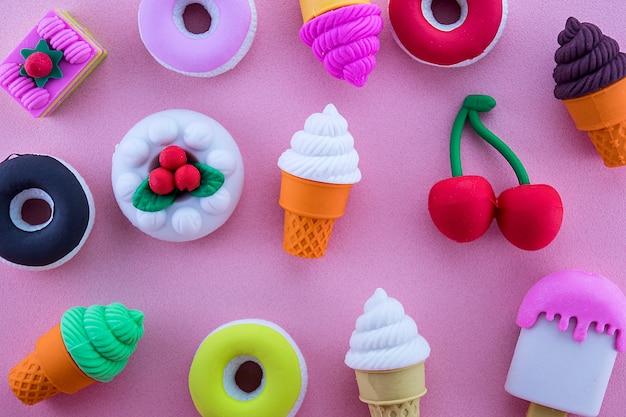 Słodycze wypełnione obfitością lody, ciasto, czereśnie, pączki. na różowym tle
