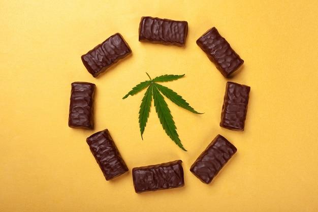 Słodycze z marihuaną, koło czekoladek z liściem medycznych canabis na żółtym tle widok z góry.
