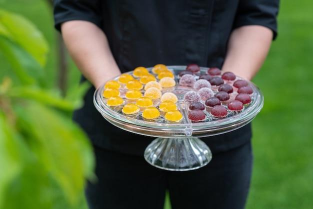 Słodycze z owoców i jagód, galaretki na przezroczystym szklanym cieście stoją w rękach szefa kuchni.