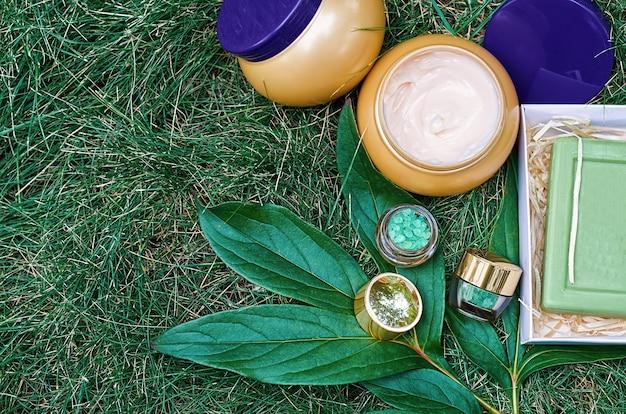 Słoiczki kosmetyczne z kremem do twarzy, kremem do ciała i solą morską na zielonej trawie.