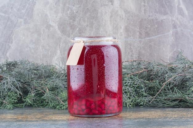 Słoik czerwonego soku na marmurowym tle. zdjęcie wysokiej jakości