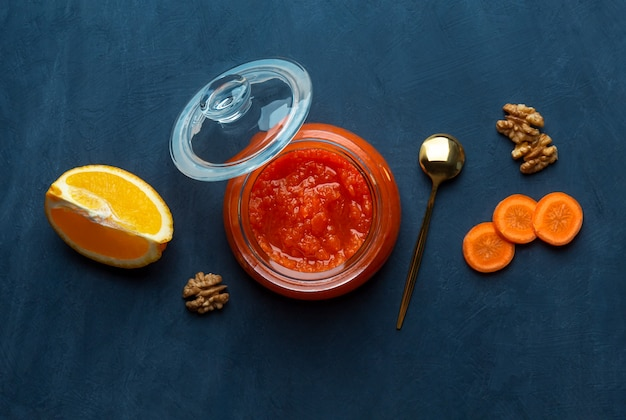 Słoik dżemu marchwiowego i pomarańczy na ciemnym niebieskim tle