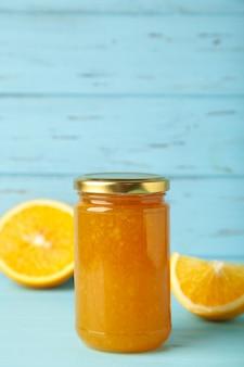 Słoik dżemu pomarańczowego na niebieskim tle. zdjęcie pionowe. widok z góry