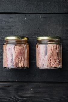 Słoik fileta z tuńczyka w oliwie z oliwek, na czarnym drewnianym stole, widok z góry