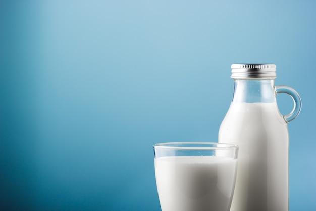 Słoik i szklanka mleka na drewnianym stole i niebieskim tle