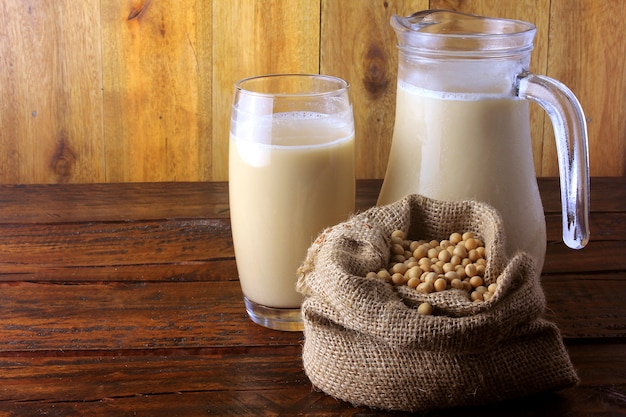 Słoik i szklany kubek ze świeżym mlekiem sojowym