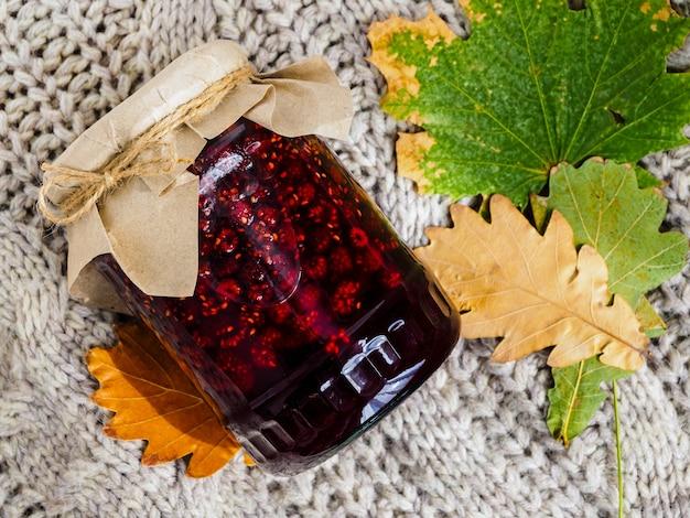 Słoik jasnej dżemu malinowego, sweter i jesienne liście. zapobieganie i leczenie przeziębień jesienią środkami ludowymi.