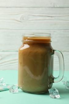Słoik kawy mrożonej, kostek lodu i słomek na stole mięty