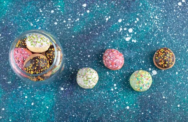 Słoik kolorowych kropi ciasteczka na niebieskim stole.