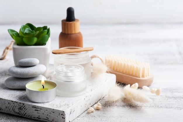 Słoik kosmetyczny z kremem, balsamem nawilżającym i olejkiem eterycznym na podłoże drewniane