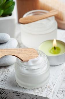 Słoik kosmetyczny z kremem, balsamem nawilżającym lub maską na podłoże drewniane. naturalne organiczne spa z ekologicznym opakowaniem