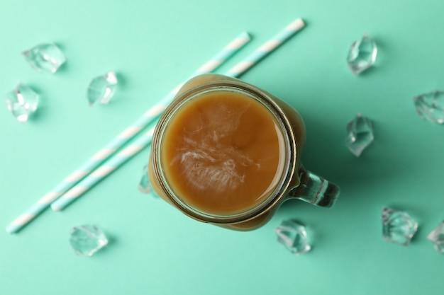 Słoik lodowej kawy, kostek lodu i słomek na tle mięty