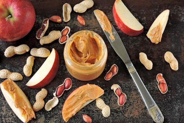Słoik masła orzechowego, orzeszki ziemne w skórce, plasterki jabłka i nóż