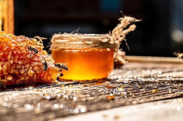Słoik miodu i plastra miodu z pszczołą latającą na drewnianym stole
