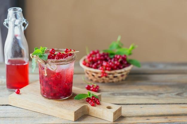 Słoik napoju sodowego z czerwonej porzeczki na drewnianym stole. letnia zdrowa lemoniada detoksykacyjna, koktajl lub inny napój. niska zawartość alkoholu, napoje bezalkoholowe, koncepcja diety wegetariańskiej lub zdrowej.