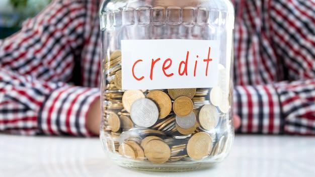Słoik pełen monet z etykietą kredyt. pojęcie finansów, wzrostu gospodarczego i oszczędności bankowych.