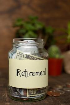 Słoik pełen pieniędzy i etykiety emerytalnej