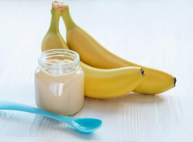 Słoik puree bananowego i bananów na drewnianym stole