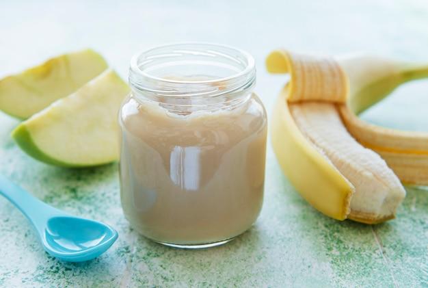 Słoik puree bananowego, jabłek i banana na zielonym drewnianym stole