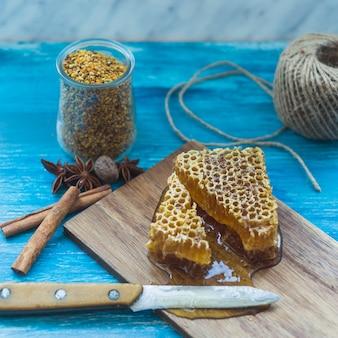 Słoik pyłku pszczelego; przyprawy i kawałek plastra miodu z nożem na desce do krojenia
