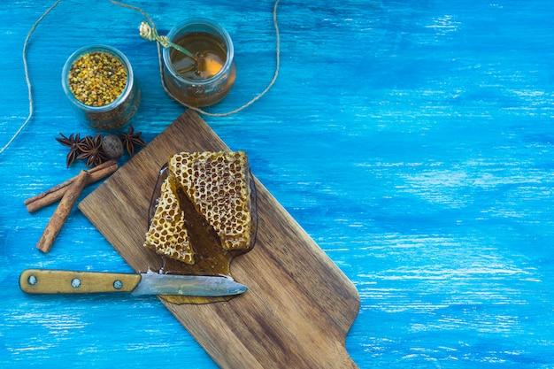 Słoik pyłku pszczelego; przyprawy i kawałek plastra miodu z nożem na niebieskim tle z teksturą
